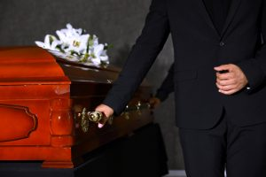 Young,Man,Carrying,Wooden,Casket,In,Funeral,Home,,Closeup